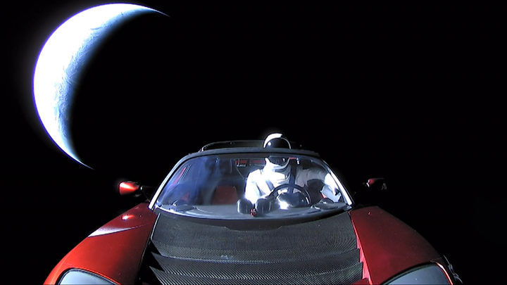 3290409 02/08/2018 SpaceX CEO Elon Musk's own car, red Tesla Roadster cabrio, entered into orbit by the Falcon Heavy launcher, with a dummy wearing a spacesuit at the steering wheel, in outer space.