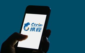 A Chinese mobile phone user shows a logo of online travel search service Ctrip,  which has more than 300 million registered users.