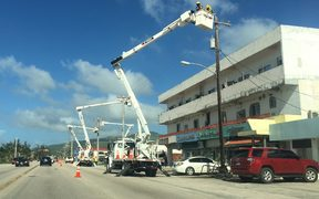 A utility crew works hard on restoring power lines on Saipan