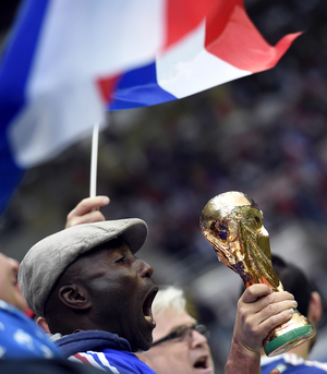 A supporter holds a fake trophy at a France/Paraguay friendly match ahead of the World Cup.