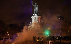 Smoke of tear gas is seen as protestors, including some wearing a yellow vest (gilet jaune), gather on Place de la Republique (Republic's Square) in Paris