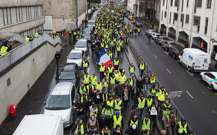 """Yellow vest"" (gilet jaune) protestors march in the streets of Tours as they take part in a demonstration to protest against the rising costs of living"