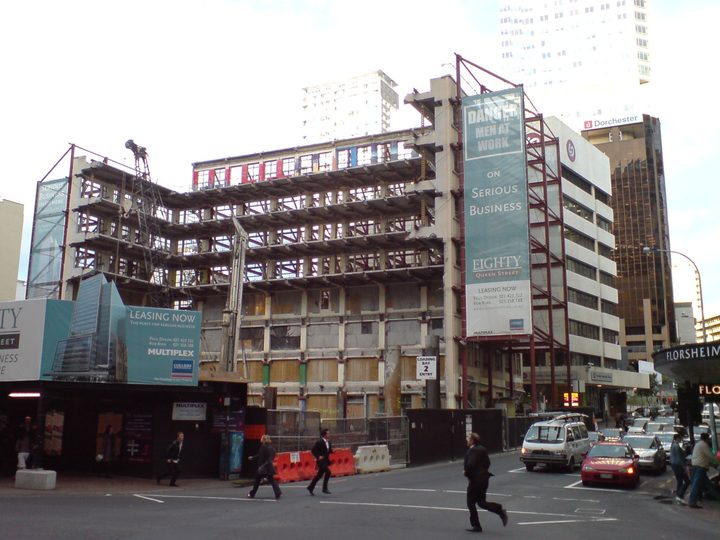 The Jean Batten building in Auckland City, New Zealand, after its almost complete demolition. Small sections were kept as part of the new skyscraper building seen on the advertisement billboard in front.
