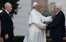 Pope Francis shakes hands with Palestinian leader Mahmoud Abbas as Israeli President Shimon Peres looks on.