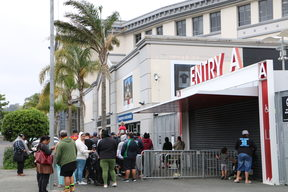 People line up outside Eden Park to collect food and Christmas gifts from Auckland City Mission.