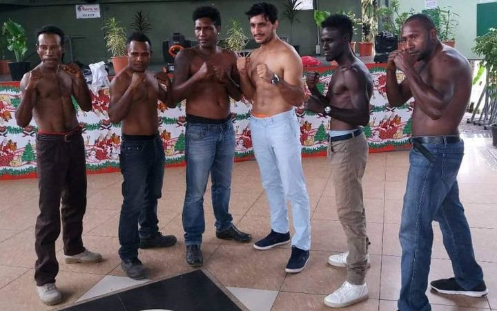 John Korake and Ezatullah Kakar (centre) pose with local boxers on the undercard.