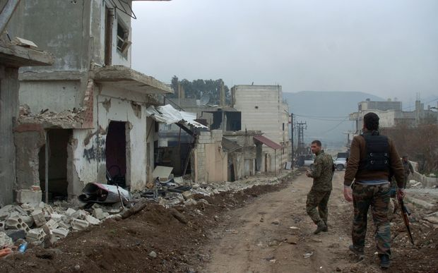 Syrian forces patrol a street in the town of Zara during fighting against rebels.