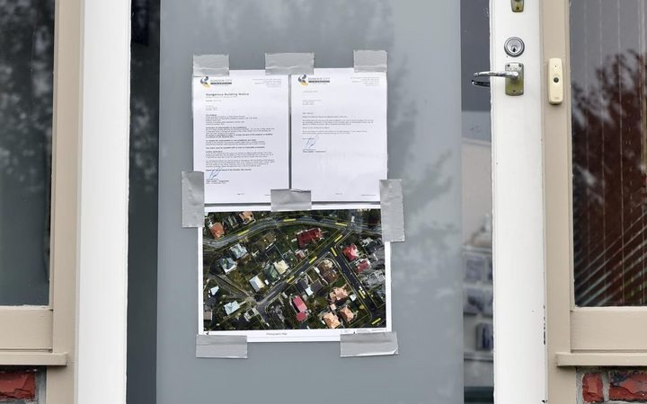 A notice on the door of a house in St Clair evacuated because of a landslip