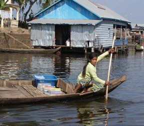 Young girl in Cambodia in canoe in front of over water tin shacks