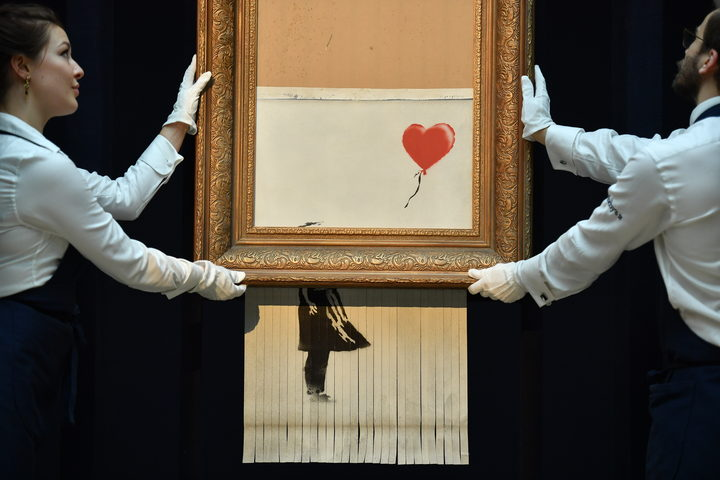 "Sotheby's employees pose with the newly completed work by artist Banksy entitled ""Love is in the Bin"", a work that was created when the painting ""Girl with Balloon"" was passed through a shredder in a surprise intervention by the artist, at Sotheby's auction house in London."