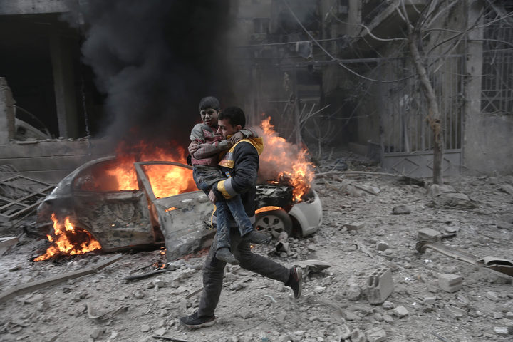 A Syrian paramedic carries an injured child following reported bombardment by Syrian and Russian forces in the rebel-held town of Hamouria, in the Eastern Ghouta.