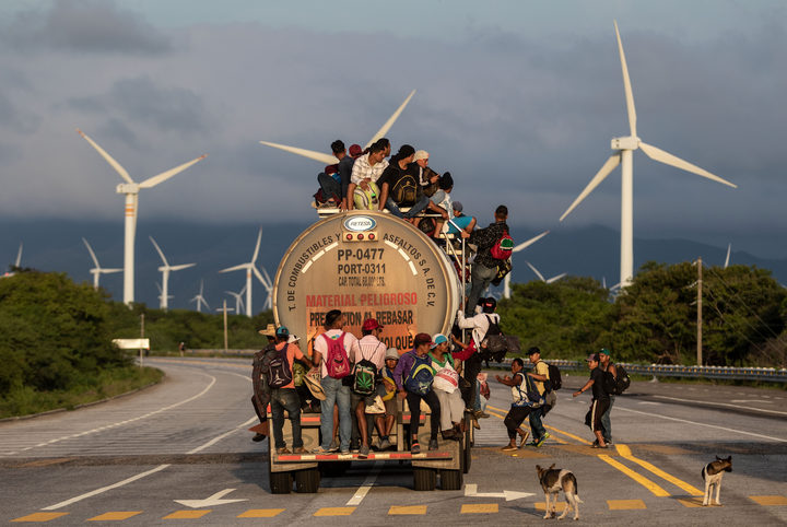 A truck carrying mostly Honduran migrants taking part in a caravan heading to the US, passes by a wind farm on their way from Santiago Niltepec to Juchitan, near the town of La Blanca in Oaxaca State, Mexico.