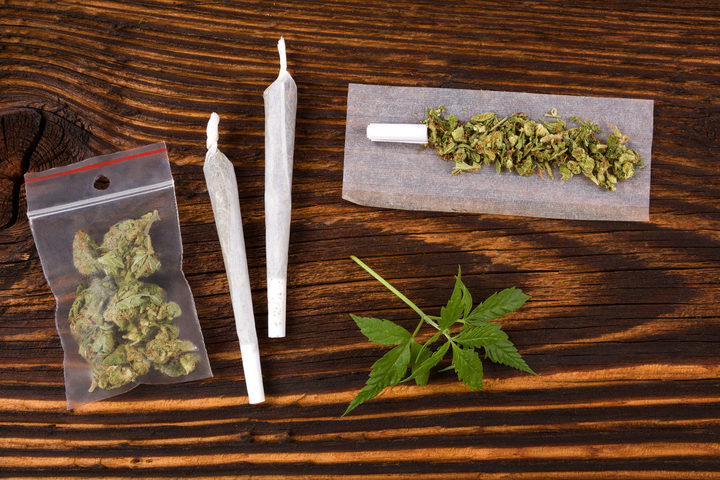 50549923 - marijuana background. cannabis joint, bud in plastic bag and hemp leaves on wooden table. addictive drug or alternative medicine.