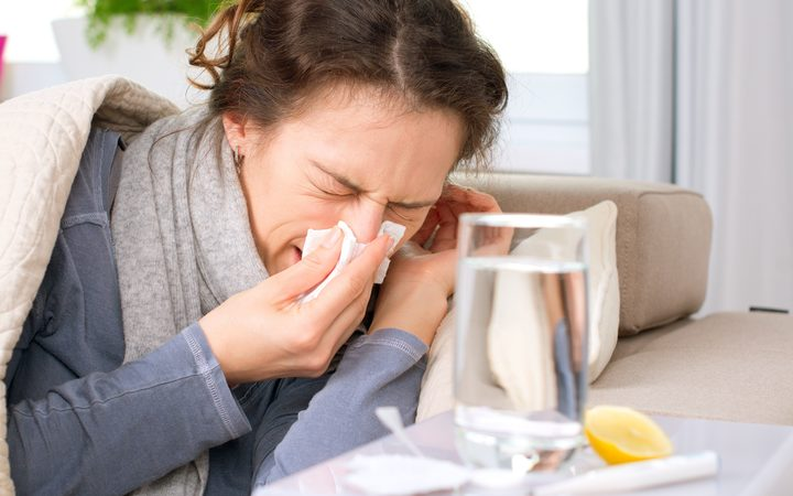 sick woman flu, cold sneezing into tissue