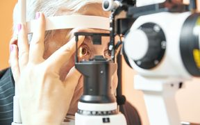 Optometry concept. Male patient under optometrist optician examinination of eyesight in eye ophthalmological clinic