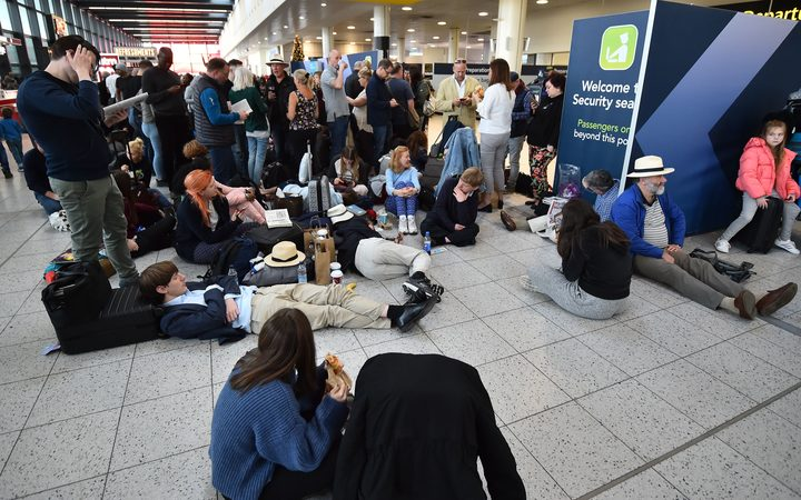 Passengers wait at Gatwick airport as police and the military try to locate two drones spotted near the runway.