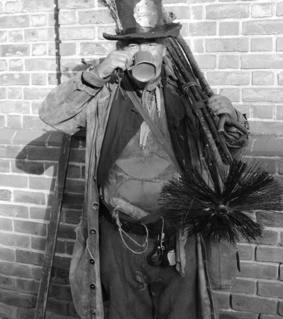 17435964 - victorian chimney sweep wearing his old clothes & carrying his brush