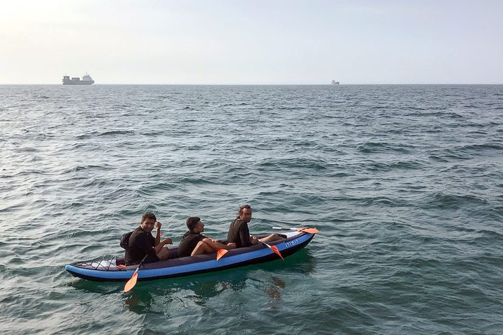 Three migrants who were attempting to cross The English Channel from France to Britain are seen as they drift in an inflatable canoe off the French coast at Calais on August 4, 2018, before being rescued.