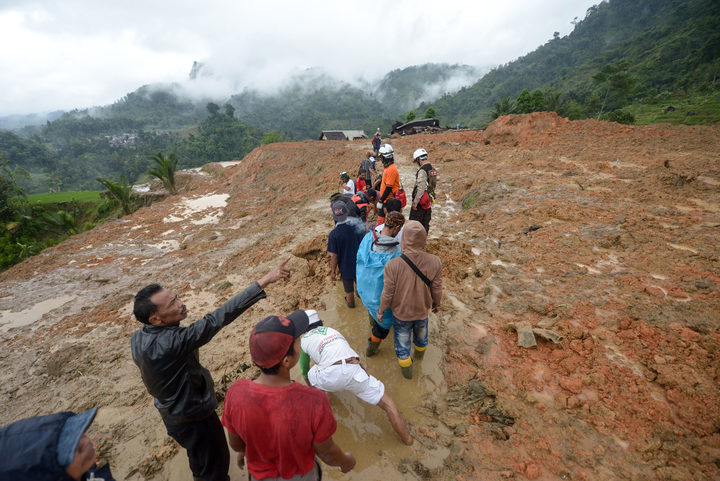 Rescue workers search for survivors at the site of a landslide triggered by heavy rain in Sukabumi, West Java province on January 1, 2019.