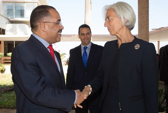 This handout photo released by the International Monetary Fund (IMF) shows IMF Managing Director Christine Lagarde (R) greeted by Mozambique's Finance Minister Manuel Chang on May 28, 2014 at the Maputo International Airport in Maputo. AFP)