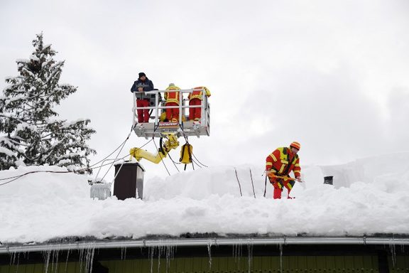 11 January 2019, Bavaria, Inzell: Firefighters clear the snow from the roof of a house. AFP