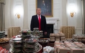 US President Donald Trump speaks alongside fast food he purchased for a ceremony honoring the 2018 College Football Playoff National Champions.