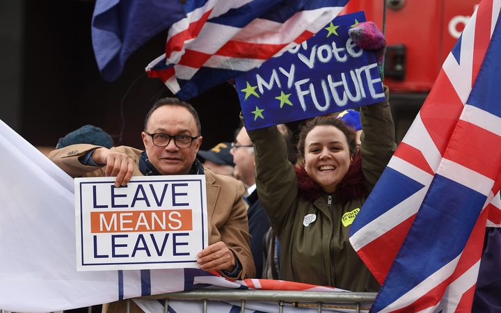 A pro-Brexit protester, left, and a supporter of a second EU referendum hold up their placards outside Parliament as MPs prepare to vote on Prime Minister Theresa May's Brexit deal.