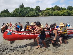 Waka being pulled up to Te Ao Hou Marae, as part of the Annual Tira Hoe Waka Whanganui River pilgrimage, January 2019.