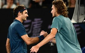 Switzerland's Roger Federer (L) shakes hands with Greece's Stefanos Tsitsipas after defeat in their men's singles match on day seven of the Australian Open tennis tournament in Melbourne on January 20, 2019.