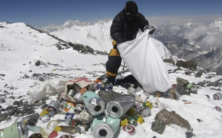 This picture taken on May 23, 2010 shows a Nepalese sherpa collecting garbage, left by climbers, at an altitude of 8,000 metres during the Everest clean-up expedition at Mount Everest. A group of 20 Nepalese climbers, including some top summiteers collected 1,800 kilograms of garbage.