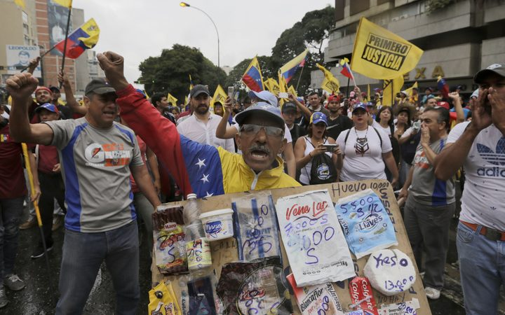 An opposition member holds a poster board with the prices of basic food during a protest against Venezuela's President Nicolas Maduro in Caracas, Venezuela.