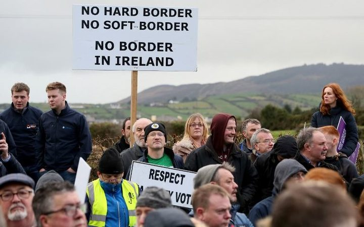 "Brexit activists hold placards as they attend a demonstration by the anit-brexit campaign group ""Border communities against Brexit"", a road crossing the border between Northern Ireland and Ireland in Newry, Northern Ireland, on January 26, 2019."