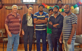 Rahul Reddy (centre) and others were visited at the Unitarian Church by Jacinda Ardern, who promised help.
