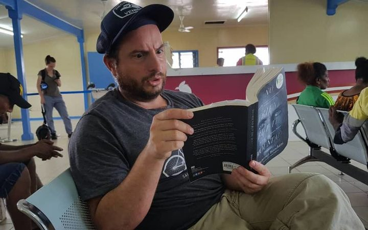 Dan Ilic reading Behrouz Boochani's book at the Manus airport.