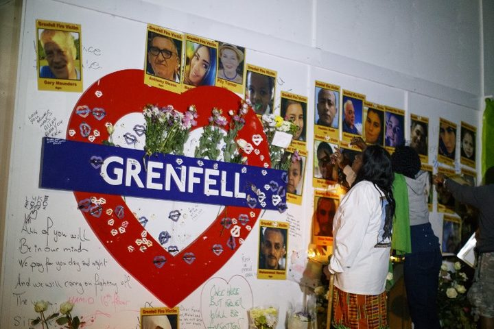 People look at pictures of the victims as members of the public hold a vigil and commemoration near Grenfell Tower in west London at midnight June 14, 2018 to honour the 71 people who died when a fire ripped through the Grenfell tower block in London one year ago.
