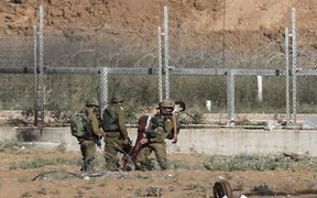 Israeli soldiers carry away an injured Palestinian who tried to approach the border fence east of Jabalia in the northern Gaza Strip on June 27, 2018.