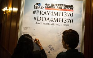A visitor adds a message for missing passengers at an International Search and Rescue Conference and Exhibition in Kuala Lumpur on Tuesday.