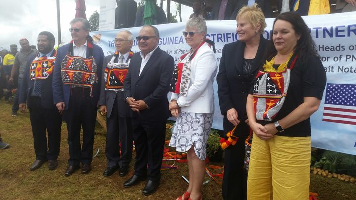 PNG prime minister Peter O'Neill (middle with shaded glasses) surrounded by diplomats (including New Zealand's High Commissioner Sue Mackwell in white jacket) and PNG Power managing director Carolyn Blacklock (far right)  officially launches a $US1.7 billion electrification project for PNG in Okapa