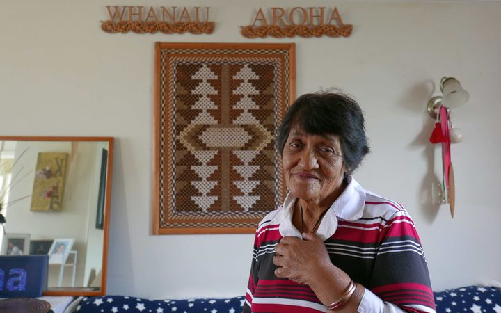 "Older woman at home with  carving behind saying ""whanau"" and ""aroha"""