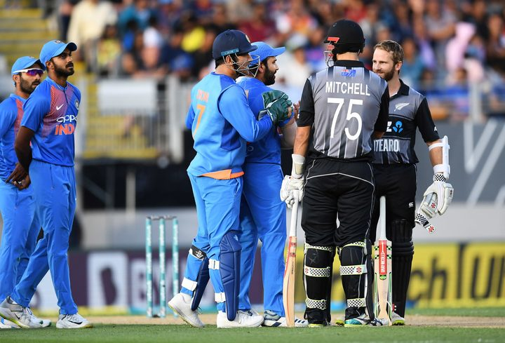 Daryl Mitchell is given out as Kane Williamson and India's MS Dhoni and Rohit Sharma look on.