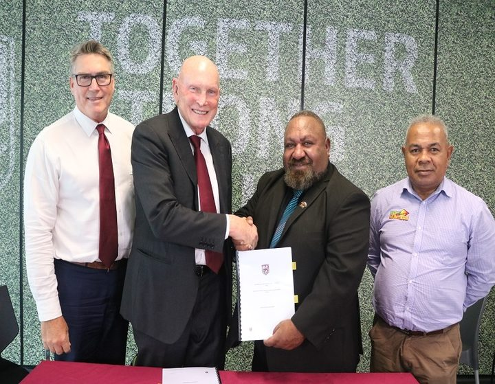 QRL Chairman Bruce Hatcher (2L) and PNGRFL Chairman Sandis Tsaka shake hands after signing a new participation agreement.