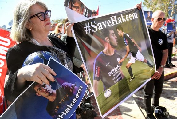 People hold up banners at a rally in Melbourne on February 2, 2019, supporting Bahraini refugee footballer Hakeem al-Araibi who was detained by Thai immigration authorities in late November after arriving in Bangkok from Australia for a vacation with his wife. -