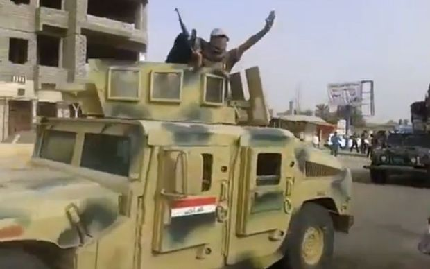 An image taken from a video put on YouTube on Tuesday allegedly showing ISIS militants parading with an Iraqi army vehicle in the northern city of Baiji.