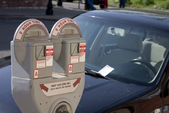 6998921 - parking meter with a car in the background with a ticket on the windshield