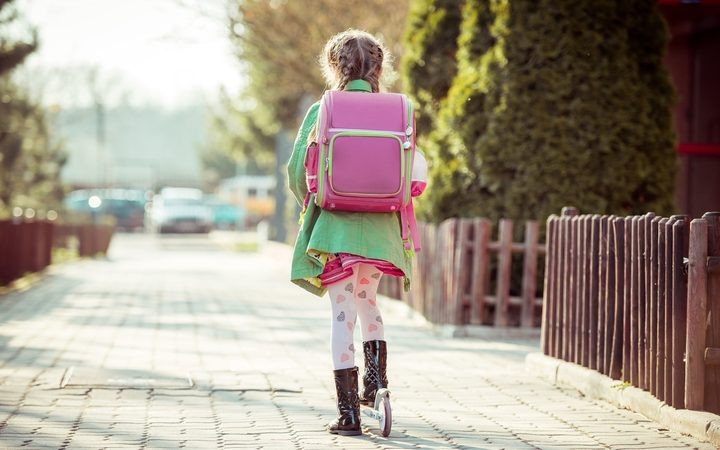 girl goes to school on a scooter. back view