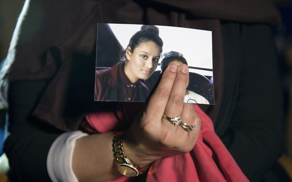 In this file photo taken on February 22, 2015 Renu Begum, eldest sister of missing British girl Shamima Begum, holds a picture of her sister while being interviewed by the media in central London