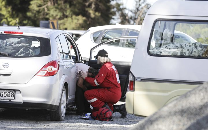 Red Cross worker supports fire evacuee at a road block