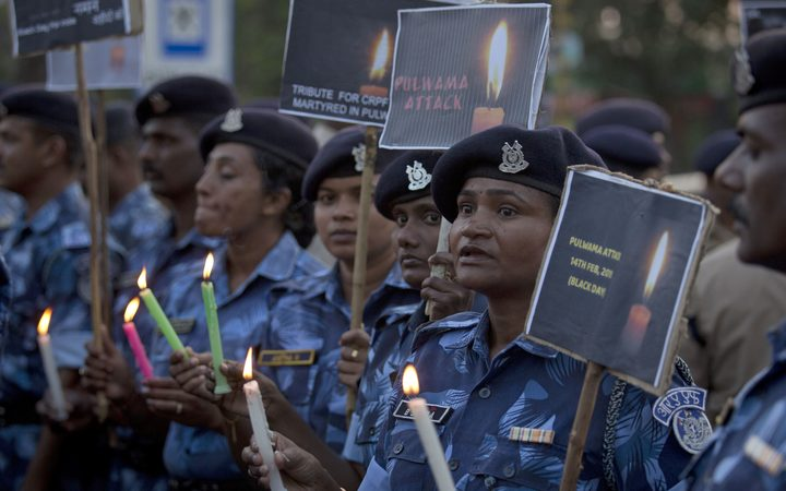 Central Reserve Police Force (CRPF) soldiers hold candles and pay tribute to their colleagues killed in Thursday's attack on a paramilitary convoy in Kashmir, in Hyderabad, India.