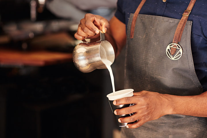 Cropped image of an African barista carefully pouring milk from a stainless steel jug into a takeaway cup in a coffee shop