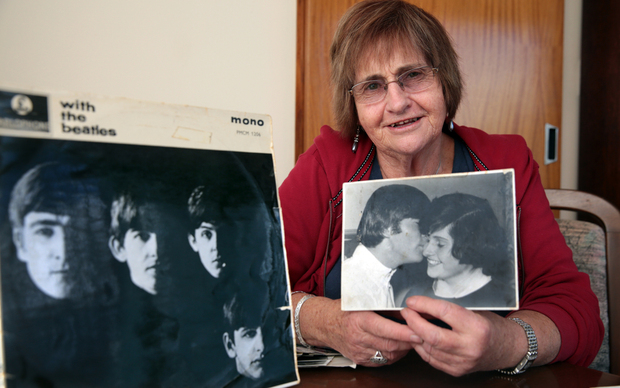 Lynda Mathews holding the photo with John Lennon.